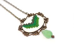 Un Pic de Traditional III - This traditional-inspired necklace is made using the applique technique in polymer clay. The pendant has a bronze metal, vintage like, base; and a matte white, polymer clay cabochon, decorated with different shades of green stitches; Embellished with a tear shaped, frozen green, glass crystal. It's tied up with a bronze metal chain. So chic! Click image to find more cool handmade jewelry by me! #necklace #polymer #clay #applique #crossstitch #traditional