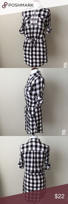 Like New Mimi Chica Plaid Shirtdress Like new! Tags removed but never worn.  Super cute Mimi Chica black, white & red plaid shirt dress with a tie at the waist, roll tab sleeves and pockets! The bottom skirt portion is lined - 100% polyester.  There is a snag on the front and some tearing of the material at the buttons on the front - I actually purchased it this way b/c I didn't feel that it was super noticeable.  I circled these flaws in the last picture.  100% rayon. Mimi Chica Dresses…