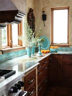 A pretty corner of a kitchen that is all aqua, dark wood, and light marble-y walls.  Overall a little too dark but this shot is so pretty.  Oranges bring in needed relief with a different color.