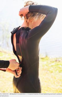 Cropped hands of man fastening woman's wetsuit at lakeshore