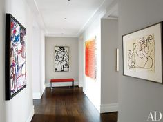 The hallway, coated in Benjamin Moore's Intense White, exhibits a Jean Dubuffet canvas, two David Smith works, and a mixed-media piece by Olga de Amara | archdigest.com