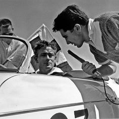 ``A serious Dean listening to famous track announcer Jim Pollack as he tells the crowd that Dean is more than an actor, but is proving himself to be a true race car driver. Dean took him to heart when he won this, his first race by 300 yards.``