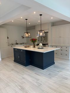 This stunning kitchen installation features light grey hand-painted cabinets with various larder tops, perfect for storing small appliances and larger food items. The contrasting dark blue island with white worktops and statement pendant lighting, along with mirrored splashback, creates a modern multi-functional family space #greykitchen #bluekitchenisland White Kitchen Worktop, Dark Blue Kitchen Cabinets, Dark Blue Kitchens, Grey Shaker Kitchen, Grey Kitchen Floor, Blue Kitchen Island, Modern Grey Kitchen, Modern Kitchen Design, Kitchen Flooring