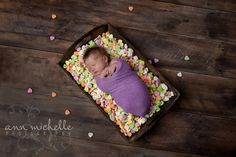 Valentine's Day newborn girl in crate of candy hearts