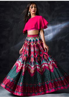 A multicoloured lehenga with abstract print in the shades of turquoise blue and fuschia pink. Moreover, teaming it with a unique cape-style hot pink blouse gives the outfit a perfect finishing. Hot Pink Lehenga with abstract print Indian Gowns Dresses, Indian Fashion Dresses, Dress Indian Style, Indian Designer Outfits, Fashion Outfits, Indian Wear, Bridal Dresses, Trendy Outfits, Choli Designs