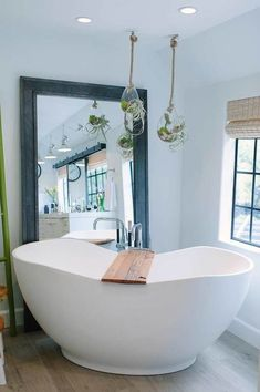 A freestanding tub fitted with a polished nickel tub filler sits catty corner on wide plank wood floor tiles under terrarium hanging vases hung in front of a black metal beveled leaning floor mirror and a black window dressed in a bamboo roman shade. Big Bathtub, Big Tub, Bathtub Caddy, Large Tub, Bathtub Ideas, Ikea Linnmon, Leaning Floor Mirror, Stand Alone Tub, Home Decor