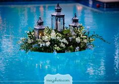 Wow! That's pretty. Floating arrangement with lanterns and flowers. Great for an outside wedding or holiday event.