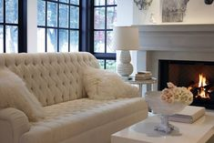 Serene, monochromatic living room with an ivory button tufted sette