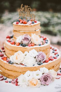 naked cake topped with berries and flowers