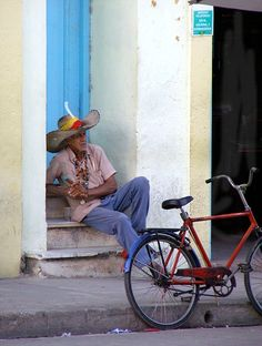man sting on a step with his bicycle in Camaguey, Cuba (own photo)