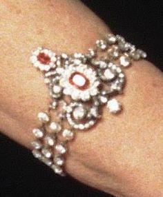 """Cuando en 1890 fallece el Rey, la Reina Emma luce el conjunto """"en blanco"""", es decir, solo con diamantes. Y una vez finalizado el luto, decide eliminar la pieza central del collar, por considerarlo demasiado """"ostentoso"""", haciendo con esa pieza un broche tipo corsage. El aderezo, al que se le pueden sustituir los rubies por otras piedras, es heredado por la Reina Guillermina I"""