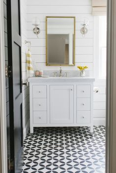 Coastal #bathroom with black and white #tile floor and white vanity
