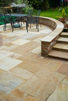 Relax outdoors in a stylish, paved entertaining area. Shown here: Fossil Cream sandstone paving