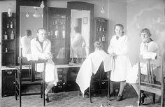 Valkoiset työtakit ja tarkkaan asetellut kampaukset on ikuistettu Parturi-kampaamossa Kuninkaankartanonkadulla. Työntekijämuotokuvassa on mukana myös asiakas, mutta hän toimii vain työn rekvisiittana ja on selin kuvassa.   Kampaajia, partureita ja peruukintekijöitä oli Turussa 138 henkilöä vuonna 1934. Ala oli työllistänyt edellisellä vuosikymmenellä vain kymmenisen henkilöä, mikä kertoo alan kasvusta. Kuvaaja: H. Attila, 1929  VA9810:3789