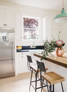 danish modern kitchen renovation with white cabinets, black granite counter tops, and butchers block island