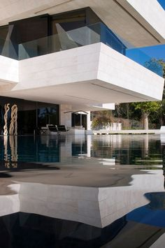 i love the play of forms and textures: water below, glass and the solid mass of the cantilevered deck. :)  Marbella, Spain.
