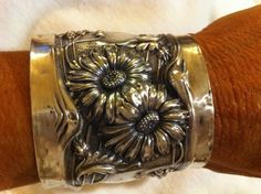 Sterling silver sunflower or daisy cuff bracelet wide big but light weight from antique brush back. $750.00, via Etsy.
