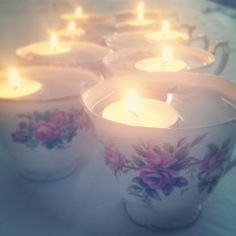 Vintage tea cups with floating candles.