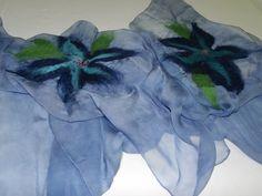 Linda echarpe de seda gaze, 100% pura, pintada à mão, com aplicação de lã merino através do processo de feltragem molhada (wet felt). Essa peça, totalmente artesanal, é capaz de agregar muito charme e sedução a qualquer visual. Em tons azuis, com duas flores aplicadas também nos mesmos tons e um pouco de verde.