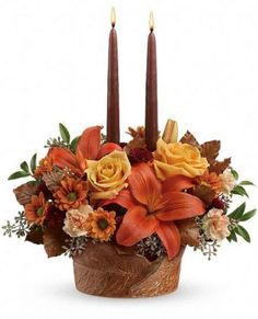 Wrapped in Autumn Centerpiece T13T100A This Thanksgiving, wrap someone in the warm glow of your love with this beautiful rose and lily centerpiece, arranged in our limited-edition oven-to-table stoneware bowl.   Lovely orange roses, asiatic lilies, miniature carnations and daisy chrysanthemums are arranged with burgundy button chrysanthemums, seeded eucalyptus, brown copper beech and huckleberry beneath two elegant brown taper candles.  by 4165flower.com