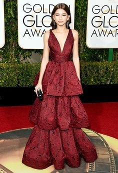 Zendaya wears a dark red lace tiered Marches gown with chandelier earrings