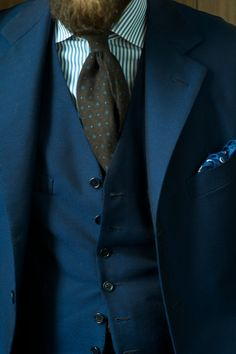 Navy suit, white shirt with blue dress stripes, brown medallion tie