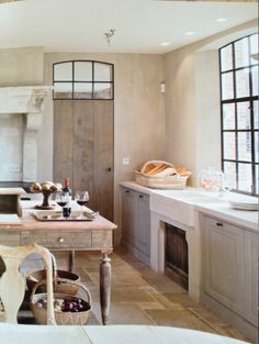 The perfect Belgian country kitchen!  Love the steel windows couple with that simple wood door.  Don't you love that transom!