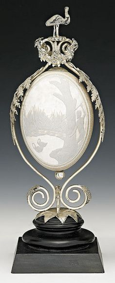 A silver mounted carved emu egg atrribued to E. Fischer, Geelong, c. The ebonised socle supporting a quadripartite scroll form base rising to frame the egg carved with a scene of an aboriginal hunting swans. Carved Eggs, Art Carved, Art Decor, Decoration, Emu Egg, Fabrege Eggs, Egg Shell Art, Style Ancien, Style Retro