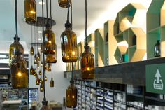 Whites Dispensary by Studio Equator, Melbourne  Bespoke large-scale 3-dimensional typographical forms were designed and hand-made as a central visual point serving as both signage and shelving. These feature shelf-letters are softly back illuminated, and positioned above the dispensary area, with medical bottles sitting on the shelves as decorative props. The sculptural letterforms are supported by custom medical bottle LED chandeliers