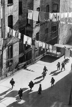 """Dec. 31, 1979: """"Youngsters in an alley near East Broadway cavorted with their shadows in crisp sunlight."""" The photographer remembers shooting the scene. """"The light and the moment were wonderful,"""" he said recently. """"The drying laundry made it memorable. You used to see laundry hung out to dry all the time in New York. Not anymore. Damn those dryers."""" Photo: Fred R. Conrad/The New York Times"""