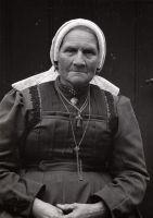 Op zondag en bij speciale gelegenheden draagt ze de cornetmuts (muts met geplooide voorstrook, met een bandje onder de kin). Bij de uiteinden van de voorstrook de mutsenbellen. Over bol en boven achterstrook ligt een pastelkleurig zijden lint met ingeweven bloemen (lintentuigje). Ze draagt een wollen lijf en rok van ouderwetse snit. Ketting met kruis (Antje Dorretein is katholiek). Zondagse kleding wordt alleen naar de kerk gedragen, daarna gauw weer uitgedaan.  #cornet #Soest #Eemland…