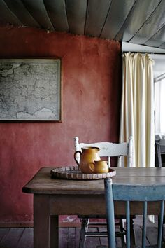lovely colors - the reddish wall with the blue chair and the golden pitchers... cozy