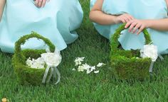 Moss covered flower girl baskets w/ a flower & ribbon accent. Get a basket & hot glue moss, messy but cute!!