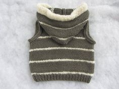 This cool baby vest/body warmer is hand knitted and made of super soft all natural merino wool (grey) combined with alpaca boucle yarn (off-white).
