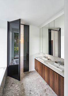 """Moderne badkamer met natuursteen vloer en houtaccenten op de kastdeuren. De """"Steel Look"""" draaideur met vast zijpaneel is gemaakt door Anyway Doors."""