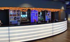 """Voici le Ghelamco Arena Lounge Bar de Gand (Belgique). Cet établissement intégré dans l'enceinte  du stade qui accueille entre autre le Club de Football La Gantoise de Gand (Koninklijke Atletieke Associatie Gent). C'est le cabinet d'architecte Bontinck qui à signé la conception de cet espace où l'ambiance apaisante est très réussit grâce entre autre aux luminaires cylindrique en bois """"Carillon"""" de chez Woodlight équipés de source Led."""