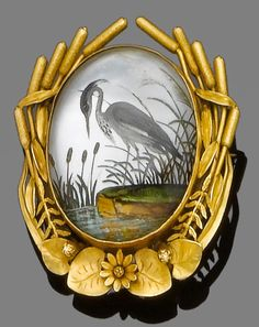 A rock crystal reverse intaglio brooch/pendant, circa 1890  The oval cabochon rock crystal carved and painted to the reverse with a stork amongst reeds, to a gold border of bull rushes and lily pads, glazed compartment to the reverse, length 4.2cm