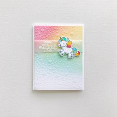 Unicorn card with multi-coloured background and sentiment on vellum.