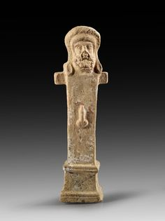 Roman pottery herm, Hellenistic, 1st century B.C. Of auburn clay with parts of white slip, the head has long hair and beard, he wears a thick wreath, high and profiled basis with a long shaft, thereupon an erected phallus, on the backside the signature CΩ, 19.8 cm high. Private collection