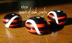 Black beads decorated with parallel red lines and a loose white wave are an Anglo-Saxon pattern dating c400 – 650AD.  Beads by Heart of Oak Crafts (Etsy).
