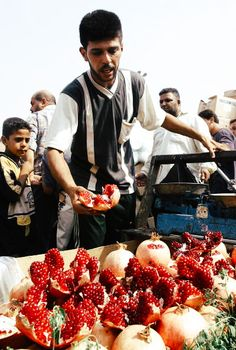 "aliirq: ""A vendor peels and displays pomegranate fruit at his stall in a market in Baghdad, Iraq, 2004. © ESSAM AL-SUDANI """