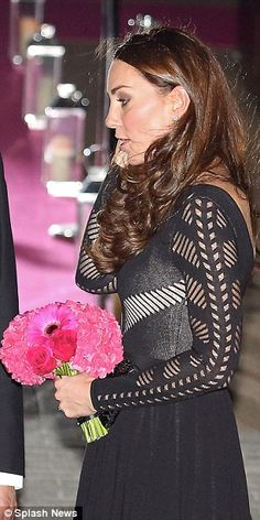 The small bouquet which included two fuchsia roses concealed the Duchess's bump as she left the event
