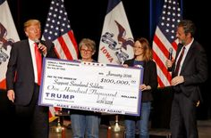 FILE - In this Jan. 31, 2016 file photo, Republican presidential candidate Donald Trump, left, presents a check to members of Support Siouxland Soldiers during a campaign event at the Orpheum Theatre in Sioux City, Iowa. Also pictured is Jerry Falwell, Jr., right, president of Liberty University.