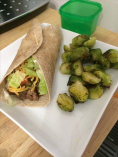 21 Day Fix Tacos! Lean ground beef seasoned with cumin, chili powder, paprika, garlic powder, onion powder, sea salt, and a dash of cayenne. Substituted Greek yogurt with a splash of lime for sour cream. Wrapped it in a whole wheat wrap with lettuce, tomato, onion, jalapeños and a half of a blue container of cheddar cheese. Roasted some brussel sprouts on the side with a tsp of evoo. 1 red, 1 yellow, 2 green, 1/2 blue, 1/2 tsp.