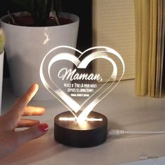 Dites à votre maman combien vous l'aimez Témoignez lui votre amour en gravant votre message Signez avec votre prénom et ceux de vos frères et sœurs Illuminez votre message avec ce cœur transparent illusion 3D  #love #heart #coeur #lamp #lampe #amour #gravure #personnalise #engraving #prenoms #gifts #giftideas #fetedesmeres Illusion 3d, Lampe 3d, Fitness Bracelet, Messages, Gravure, Place Cards, Place Card Holders, Customized Gifts, Happy Name Day