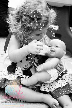 Little girl feeding her baby doll.