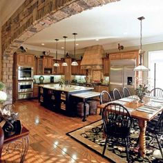 Amazing eat-in kitchen with a massive stacked-stone arch (via who took pictures of my house? / Beautiful kitchen)
