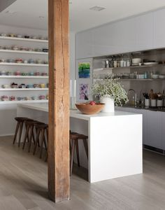 This kitchen is simple but I love the mix of all white with wood and lots of coloured bowls on the open shelving | Dumbo loft designed by Robertson and Pasanella | Remodelista