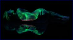 """""""Bodyscapes"""" is a body art series by artist John Poppleton """"Under Black Light"""" that uses fluorescent pigment to paint landscapes on female models. He then photographs the models under UV light for the final fluorescent effect."""