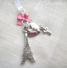 A cute phone dust plug charm with French theme. A silver Eiffel tower charm and a heart locket charm with a small key, hanging from a lovely pink bow.     Who doesn't love the city of romance, Paris, and the iconic Eiffel tower. Now you can decorate your phone with it, using this beautiful charm....